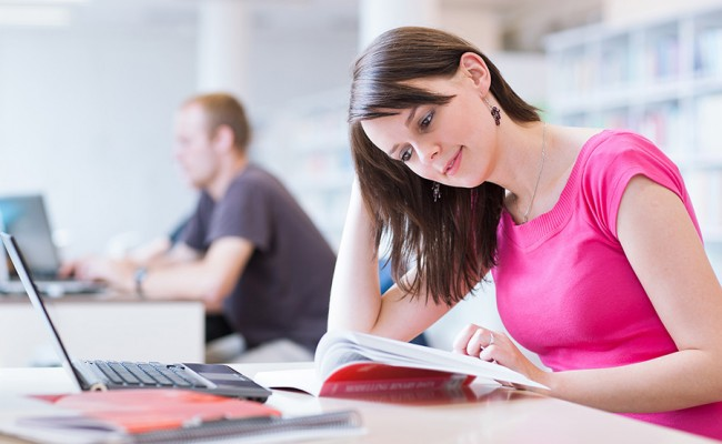 in the library – pretty female student with laptop and books wor